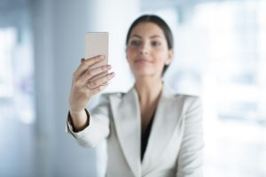 Closeup of content beautiful middle-aged business woman taking selfie on smartphone with focus on hand