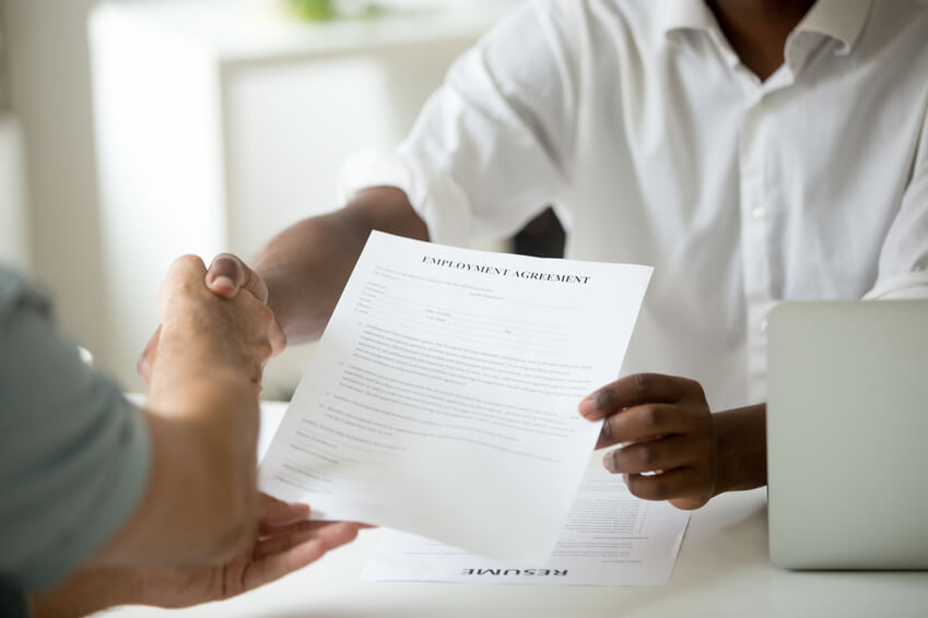 African american employer holding employment agreement offering new job welcoming successful vacancy candidate, black recruiter and white employee shaking hands, getting hired concept, close up view